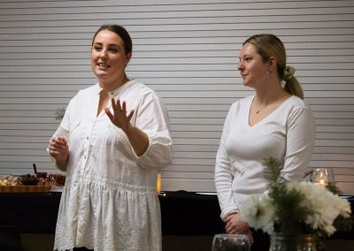 2 women giving a presentation before a meal