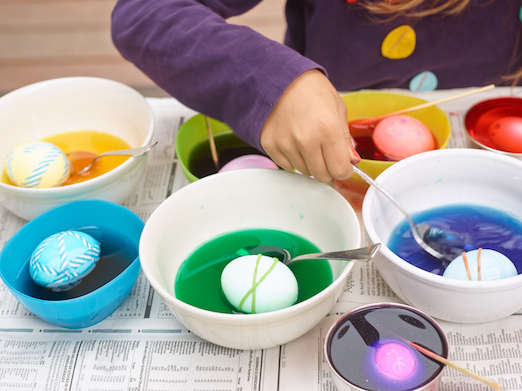 Eggs dipped into different bowls with coloured liquid inside. A hand holding a spoon scoops one out.