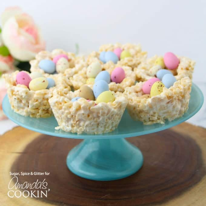 Rice Krispie Nests filled with Blue, Yellow, and Pink Mini Eggs on top of a Blue Cake Stand