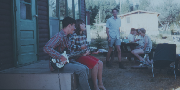 An old photo of two young people singing to a guitar