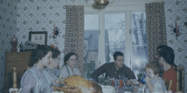 An old photo of people gathered around a table to eat