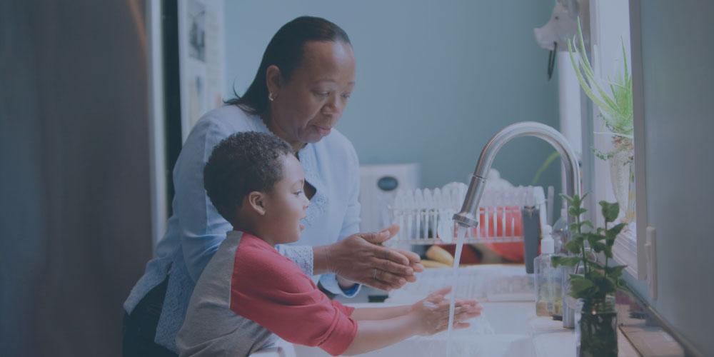Woman teaching boy to wash hands