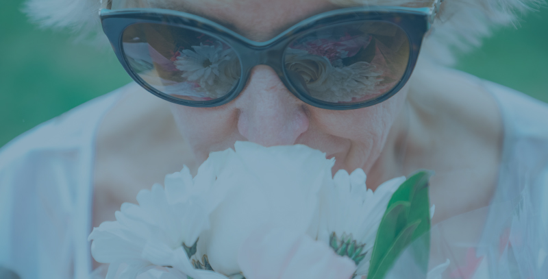 woman in black framed sunglasses smelling flowers