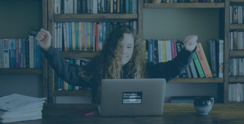 girl in black shirt doing homework on a laptop