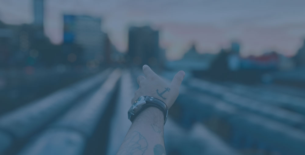 tilt shift photography of man's left hand with anchor tattoo pointing at high rise buildings