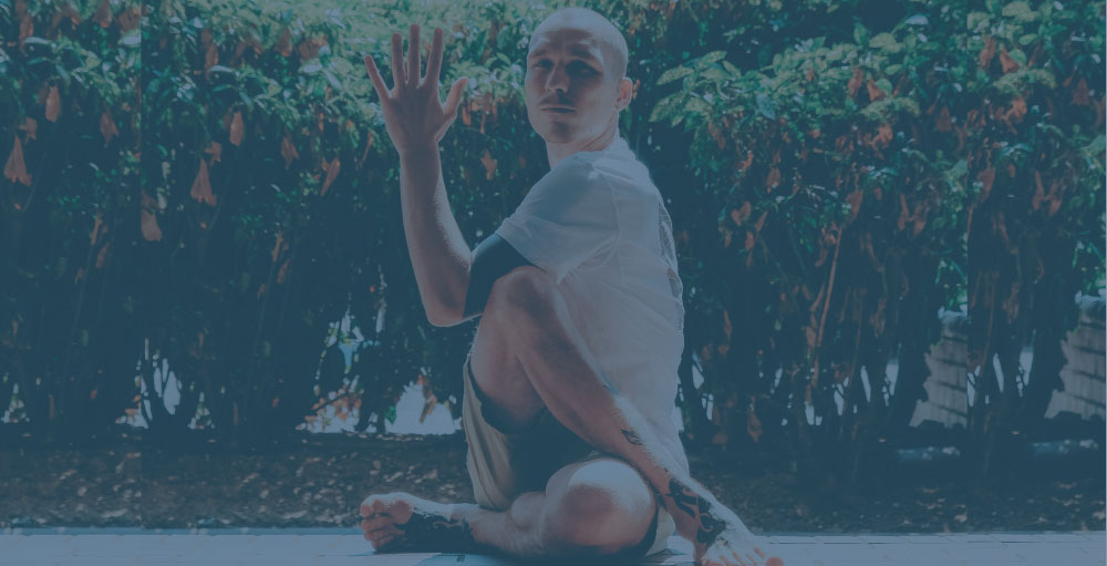 man sitting on the grounding doing yoga